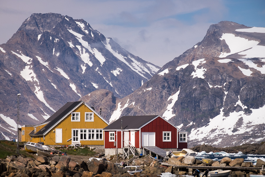 Two brightly painted houses in front of distant mountain