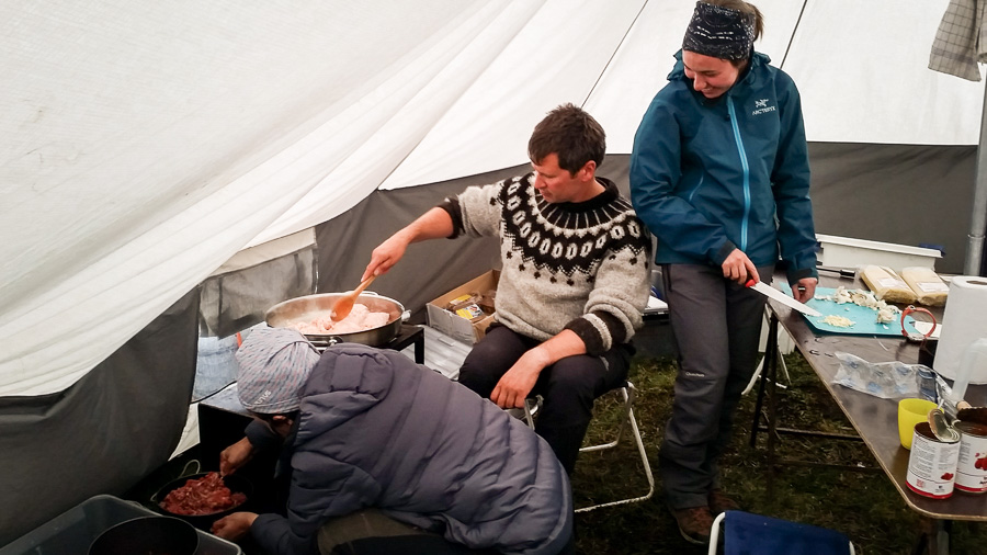 Maxime and 2 of my trekking companions preparing dinner inside the cook/dining tent