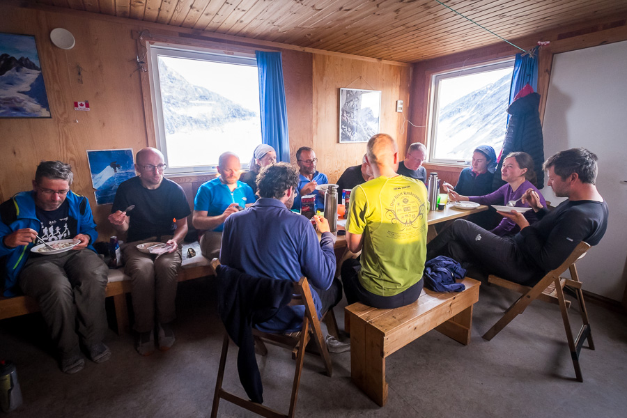 The group sitting around the dining table at Tasiilaq Mountain Hut eating lunch