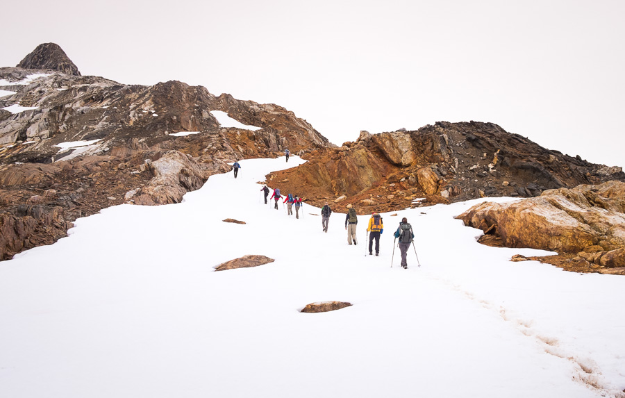 Trekking group following muddy bootprints in the snow