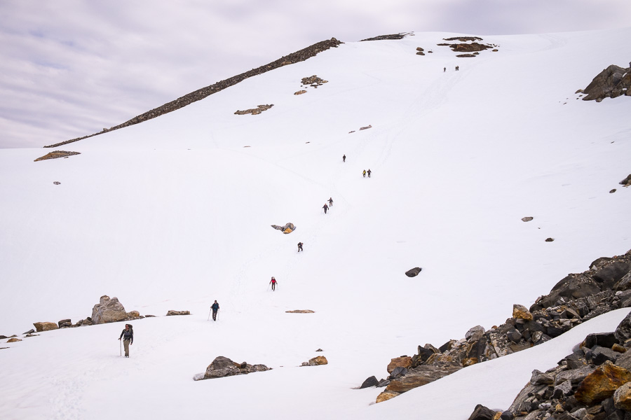 Trekking group running down the steep snowfield