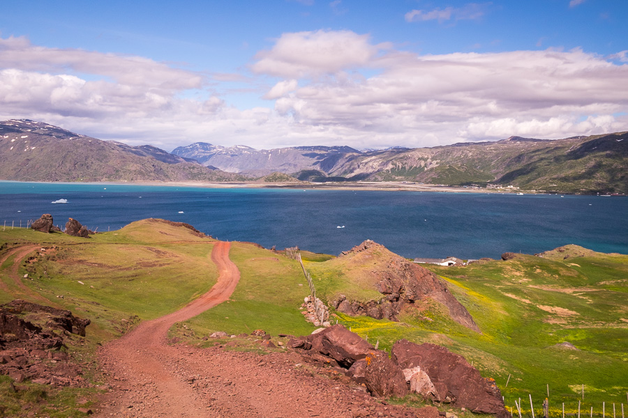 A red dirt road leads down green hills to the fjord and Qassiarsuk, South Greenland