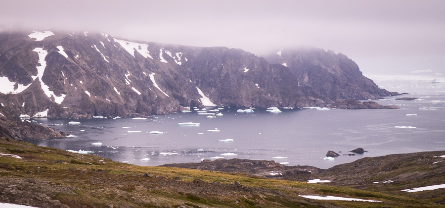Icebergs in the ocean and very low cloud. Seen while hiking from Kulusuk to Isikajia in East Greenland