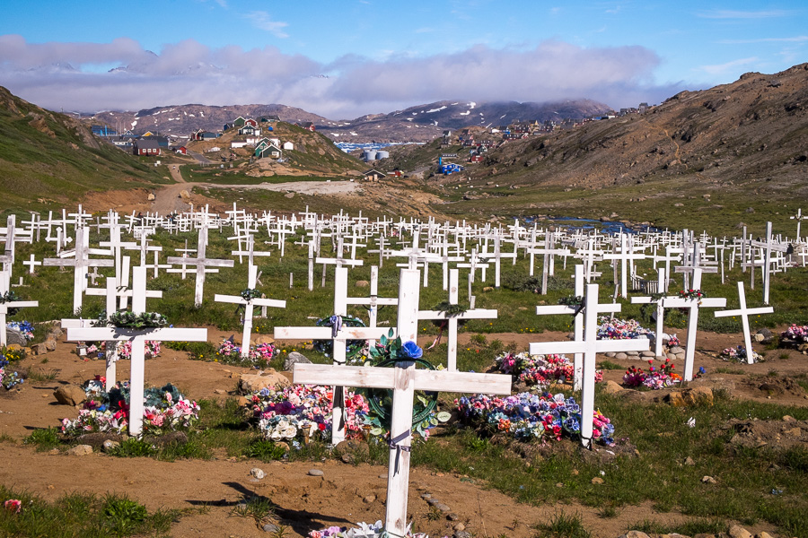 A field of white crosses and plastic flowers marking the graves in the cemetery just outside of Tasiilaq on the way to the Flower Valley