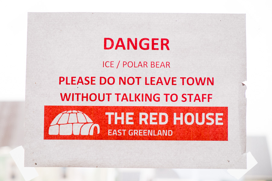 Paper sign pasted on the door as you exit the Red House, warning about leaving town without first discussing with staff