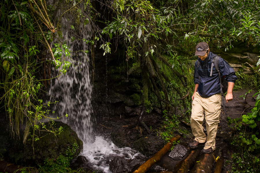 Mark and a small waterfall right beside the hiking path on the way to Cascada Condor Machay near Quito, Ecuador