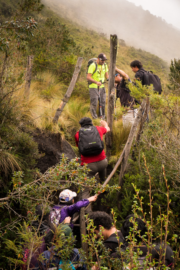 Hiking companions negotiating a fence along the hiking trail to the summit of Volcán Pasochoa near Quito, Ecuador
