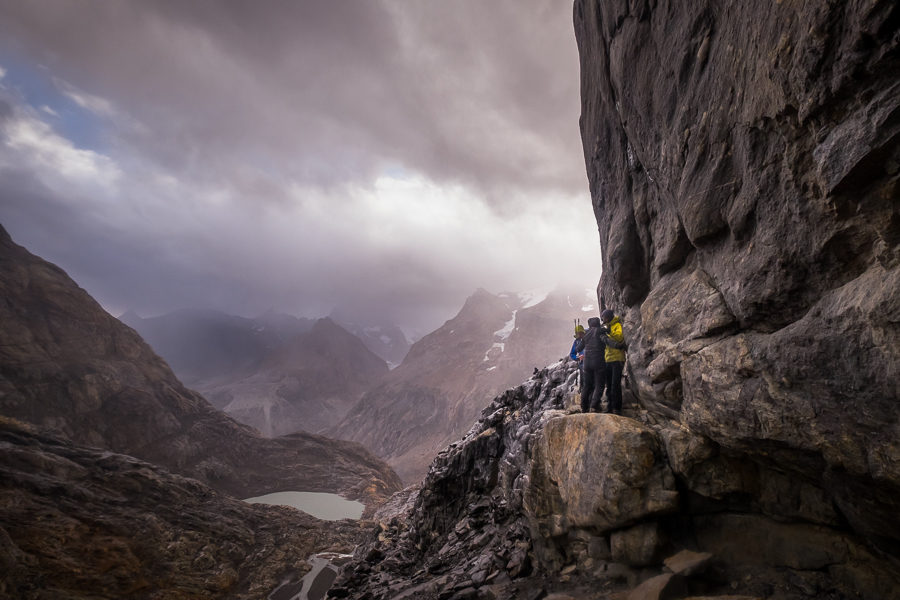 Juan helping Anita on top of a narrow ledge with a steep drop-off to the left - South Patagonia Icefield Expedition - Argentina