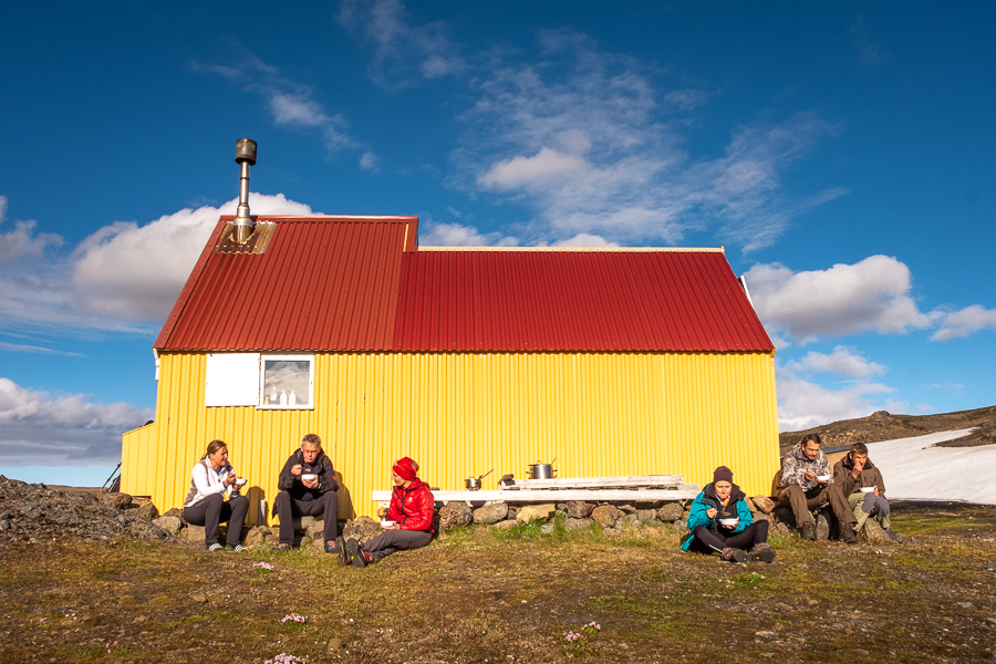 Hiking companions sitting on the ground outside the Geldingafell Hut - Shadow of Vatnajokull - East Iceland