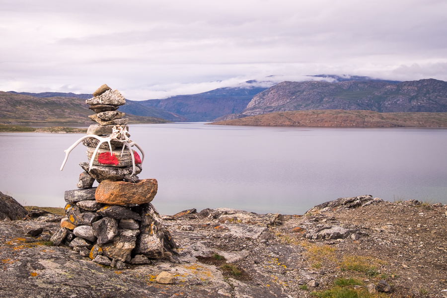 Stone cairn with reindeer antlers in front of a lake - Arctic Circle Trail - West Greenland
