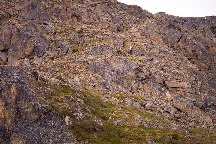 Hiker making his way up steep rocky slope - Nasaasaaq mountain - Sisimiut, West Greenland