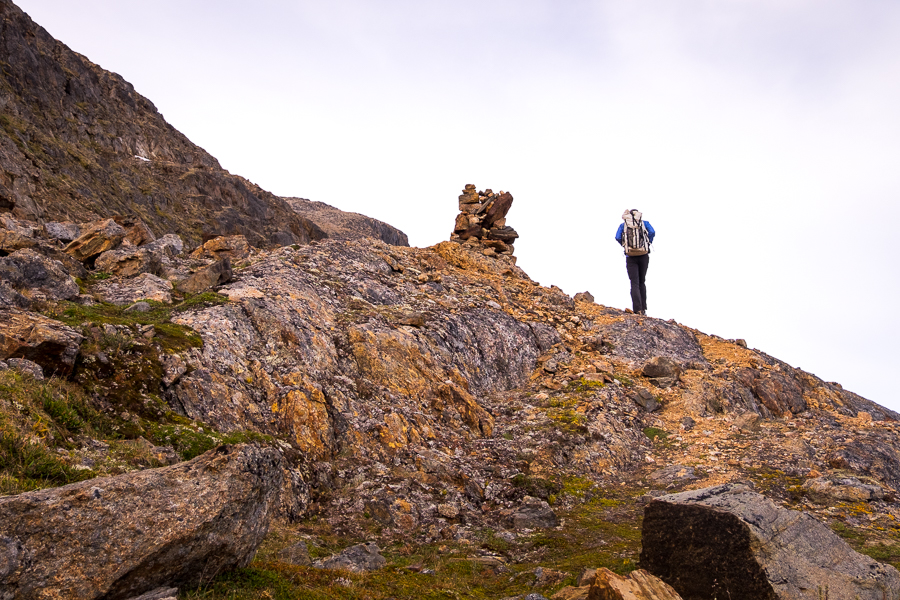 Hiker approaching a cairn on the flank of Nasaasaaq mountain - Sisimiut, West Greenland