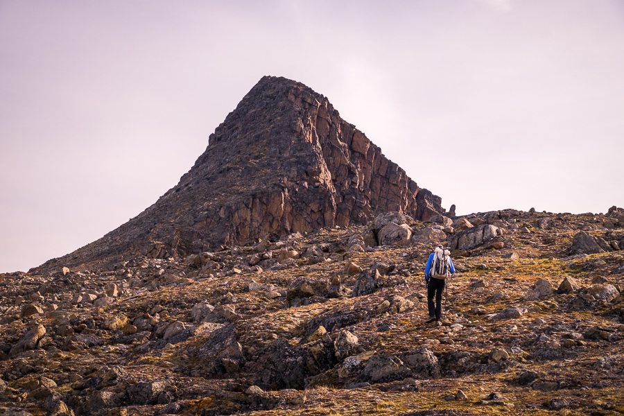 Hiker heading towards the triangular peak of Nasaasaaq mountain - Sisimiut, West Greenland