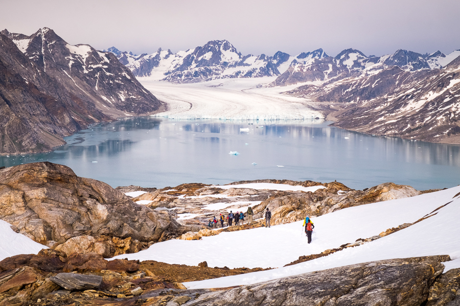 Hikers exploring the bare, rocky peaks of East Greenland with the Knud Rasmussen glacier and Karale Fjord in the background