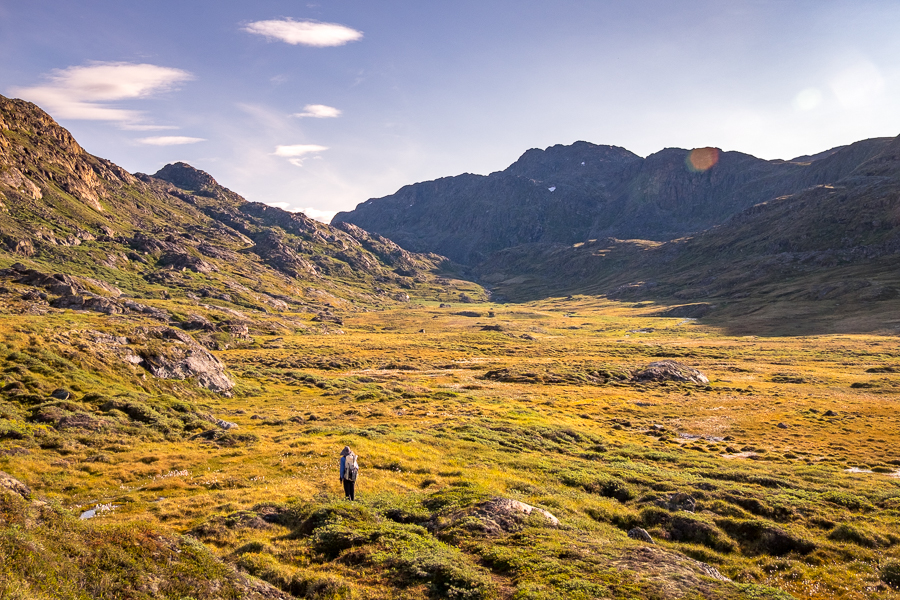 Hiker approaching the boggy ground at the bottom of the valley -  Sisimiut UFO hike - West Greenland