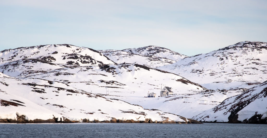 Summer home in a snowy landscape in the Nuuk Fjord, West Greenland