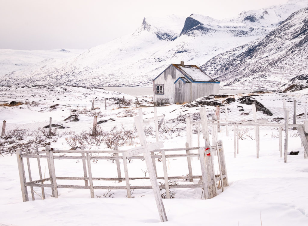 The cemetery at Qoornoq and one of its houses set against the mountainous backdrop - Nuuk Fjord - West Greenland