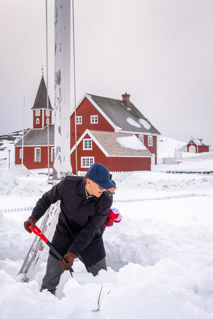 Miki shoveling snow around the flagpole - Nuuk Multi Kulti - West Greenland