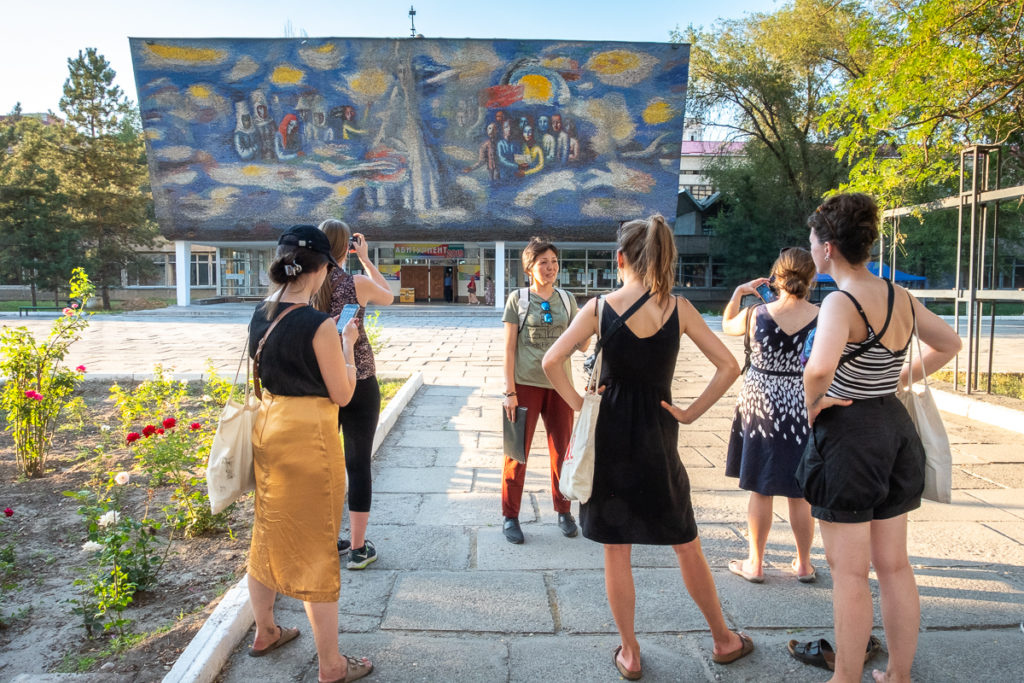 Walking tour group in front of the Path to Enlightenment mosaic - Bishkek