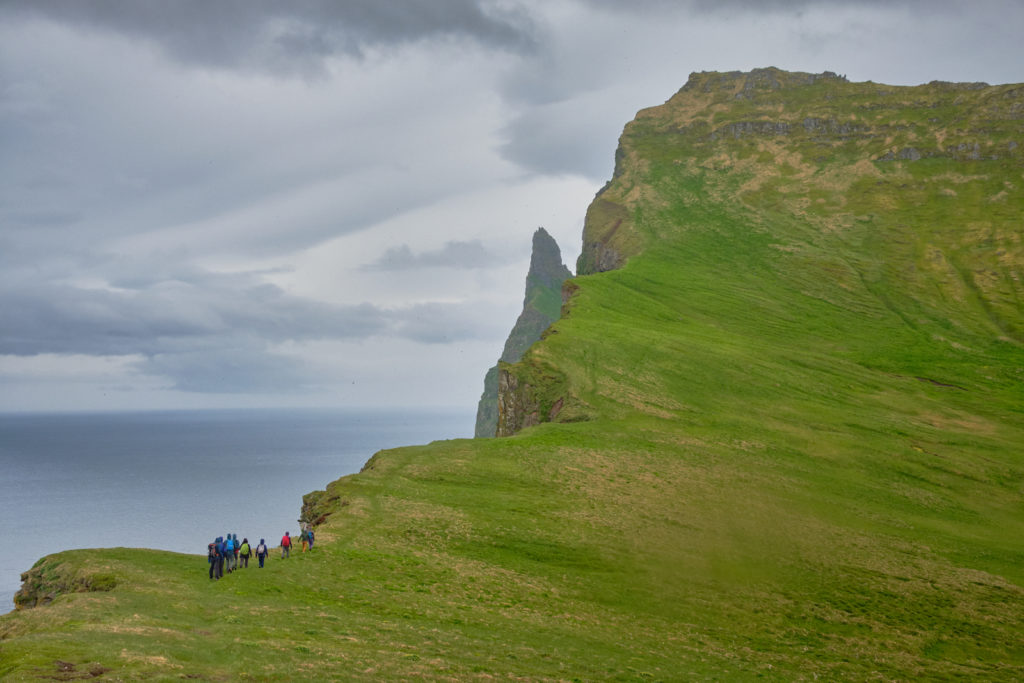 Group of hikers making their way towards the higher portion of Hornbjarg - Hornstrandir - Iceland
