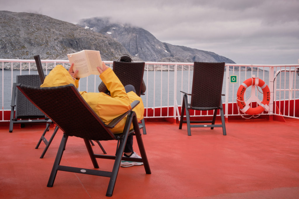 Person reading a book on the top deck of Sarfaq Ittuk, rugged up against the cold