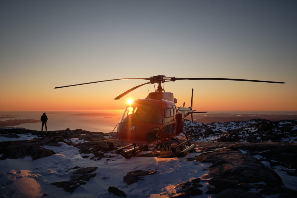 sun setting behind the helicopter on the summit flight - nuuk - West Greenland
