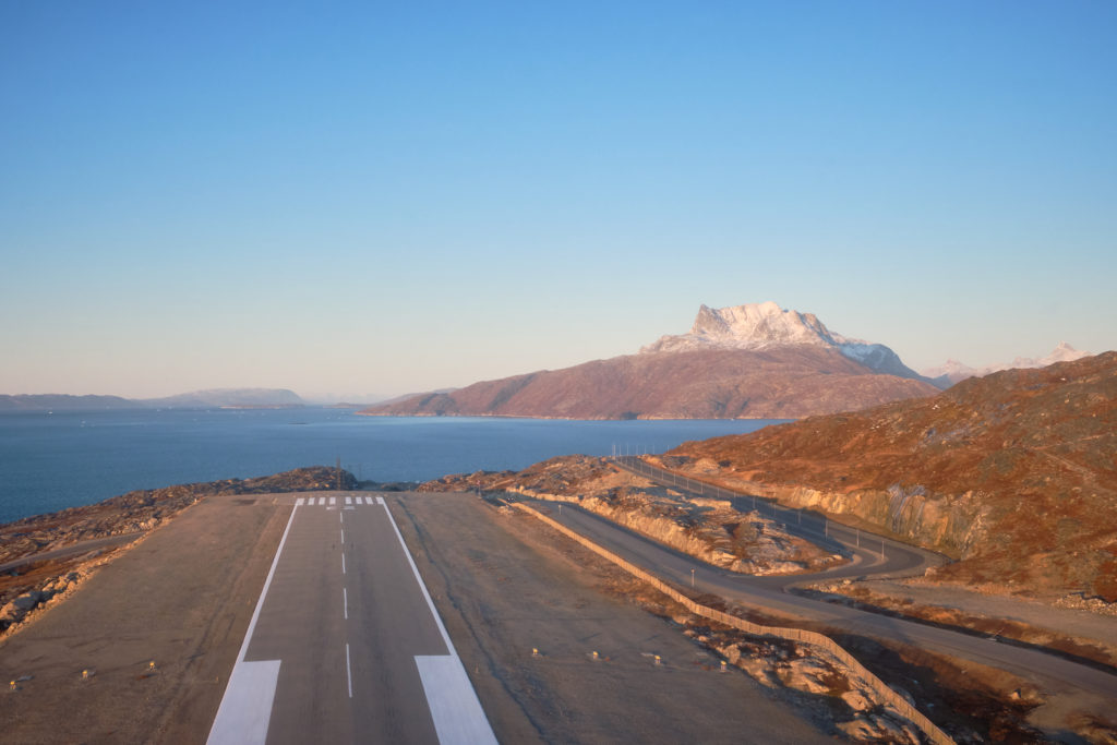 Taking off in the helicopter for the Nuuk Summit Flight. The runway at Nuuk airport and Sermitsiaq - West Greenland