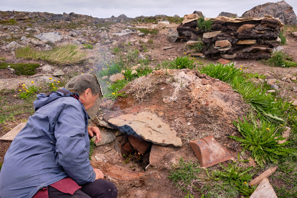 preparing the fire in the traditional smoking pit for drying fish and meat - Sassannguit - Greenland